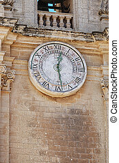 Old clock on a bell tower - Old clock with Roman numerals on...
