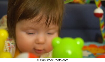 Cute little baby girl playing with toys and looking in...