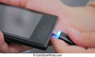 Woman's hand plugging black lightning charging cable into...