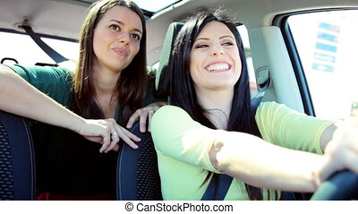 Two girlfriends driving car talking about love - people...