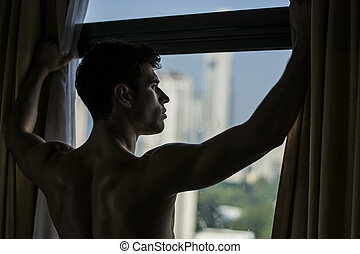 Sexy young man standing shirtless by curtains - Sexy...