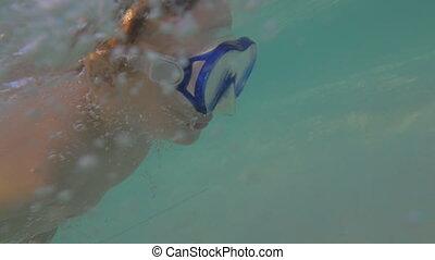 Child in snorkel mask swimming underwater