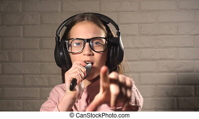 Teenager girl in headphones listening music and singing -...
