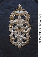 Gold metal decoration on old black door