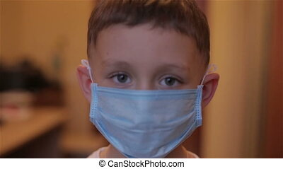 Close-up of a boy wearing a mask at a reception at the doctor