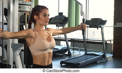 Fit woman doing exercise on chest machine in modern gym