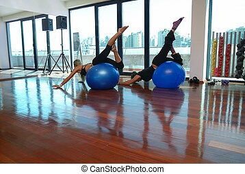 pilates - woman doing exercise with blue pilates ball
