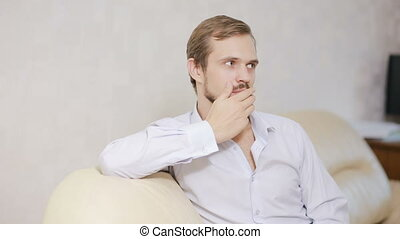 Portrait guy looking at camera on couch. Young man with...