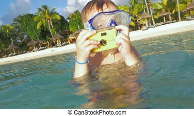 Child bathing in ocean and taking photos with waterproof...