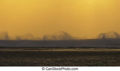 Slow motion view of ocean waves against yellow red sunset sky, Mauritius Island