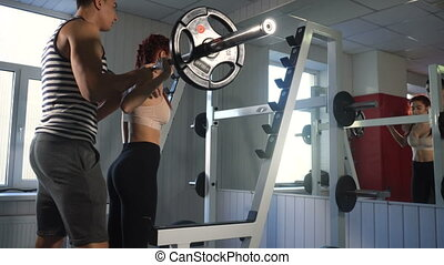 Sproty couple doing squats. Trainer helps to woman doing...
