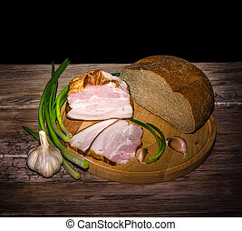 lard and bread with onion and garlic on cutting board in...