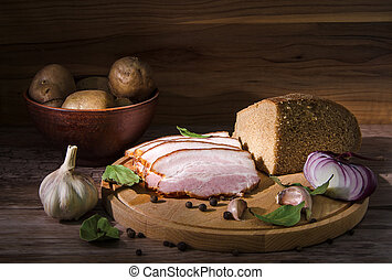 lard and bread with potatoes and spice on cutting board in...