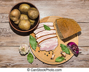 lard and bread with potatoes and spice on cutting board