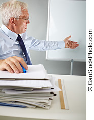 working with paper - Senior manager with papers and board on...