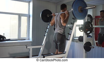 Strong man doing squats in modern gym