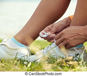 tieing shoe-laces in nature - woman sitting on grass tieing...