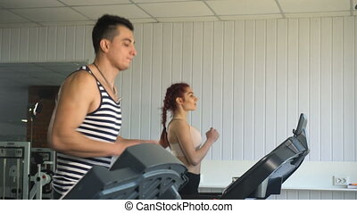 Man and woman running on treadmill - Sportsman man and woman...