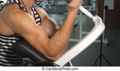Strong man doing exercise in biceps machine on his big...