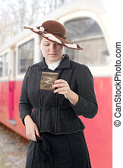 woman in vintage costume 1900s, old train background - young...