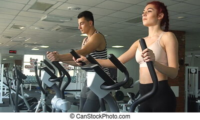 Active young man and woman using elliptical machine in gym