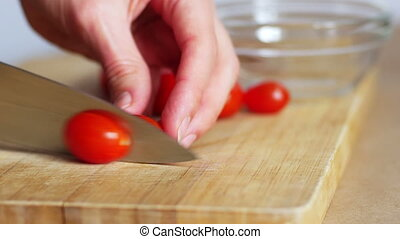 Close up of woman hands cutting cherry tomatoes and putting them in white bowl, 4k