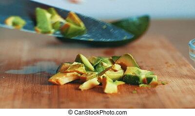 Woman cuts an avocado fruit on wooden board, graded 4k
