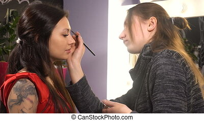 Makeup artist makes makeup for woman model with tattoo in...