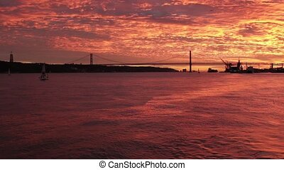 fabulous bloody sunset over Tagus river from a boat Lisbon -...