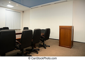 Tribune in conference room with a table and chairs