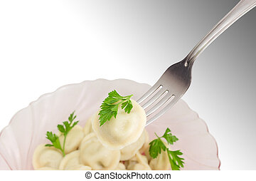 Pelmeni on fork on background of dish with pelmeni - Cooked...