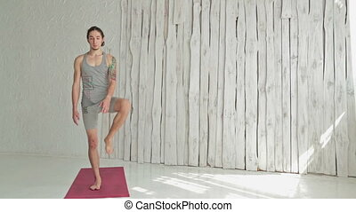 Young sporty man practicing yoga in fitness studio -...