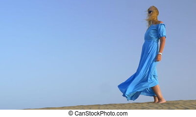 Slow motion view of young blond woman standing against blue...