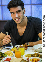 Attractive Young Man Eating Breakfast, Having a Slice of...