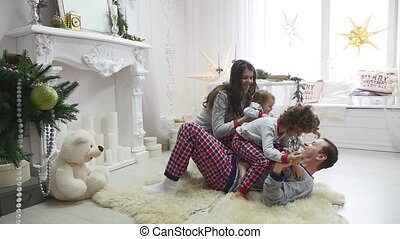 Happy young family sitting on floor at christmas morning in...