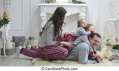 Happy young family sitting on floor at christmas morning in pajamas, smiling. Photoshoot with Flash Light