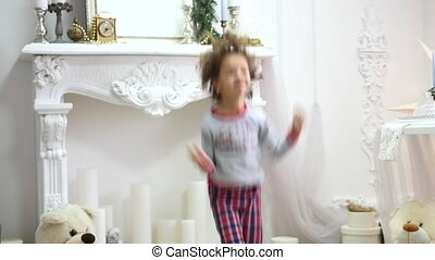girl in pajamas jumping on the bed. The concept of Christmas. Photoshoot with Flash Light