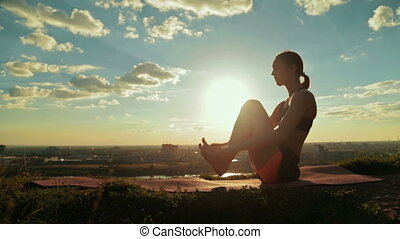 Woman doing yoga in floating boat pose in the park at sunset...