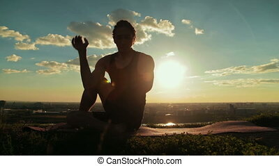 Man doing Ashtanga yoga in the forest at sunset - Silhouette...