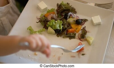 Little girl take piece of tomato on the fork from the Greek...