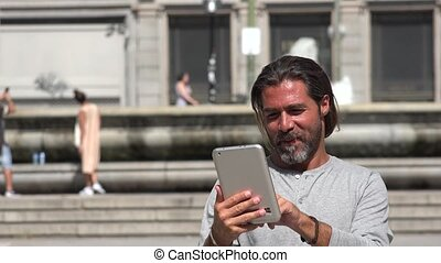 Man Walking And Using Tablet