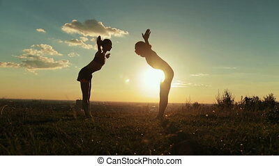 Couple doing Ashtanga yoga in the forest at sunset