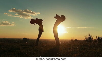 Couple practicing yoga in the park at sunset - drop back,...