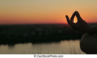 Sporty woman in lotus position in the park at sunset - Close...