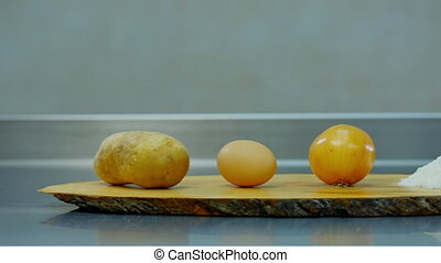 potatoes, onion, egg and flour lying on a wooden stand