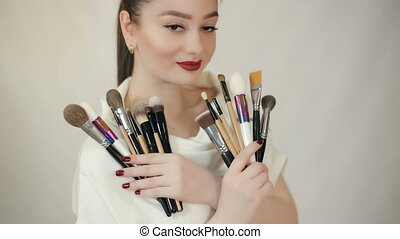Visagiste with makeup brushes - Beautiful woman with makeup...