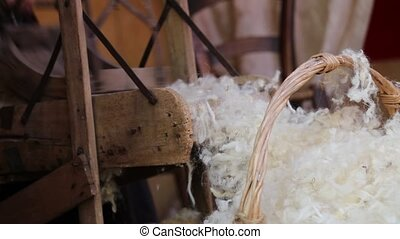 old wooden carder and raw wool