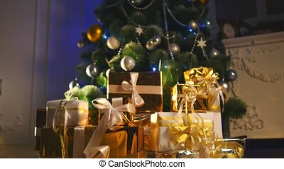 luxury gift boxes under Christmas tree, New Year home decorations, golden wrapping of Santa presents, festive fir tree decorated with garland, bauble, traditional celebration