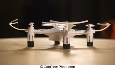 Small white drone quadrocopter blinking with lights at the...