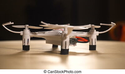 Small white drone quadrocopter blinking with lights and...
